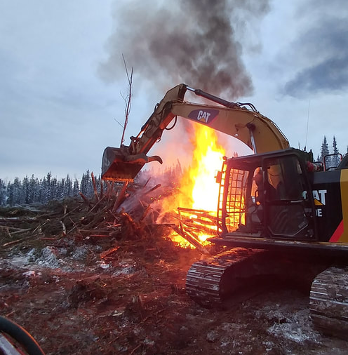 burning a brush pile with the help of an excavator